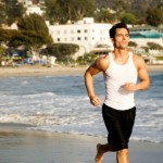 A male jogger jogging alone the beach.