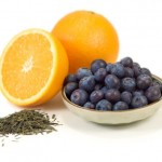 A bowl of blueberries next to a half orange, a whole orange and a pile of green tea.